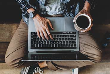 a person with a laptop holding a cup of coffee